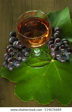 glass of wine with a cluster of red grapes on wooden table background, top view