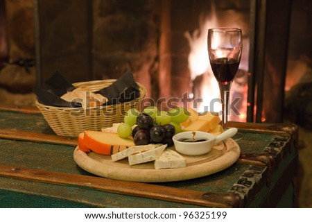 Glass of wine with bread cheese and grapes fire place in background