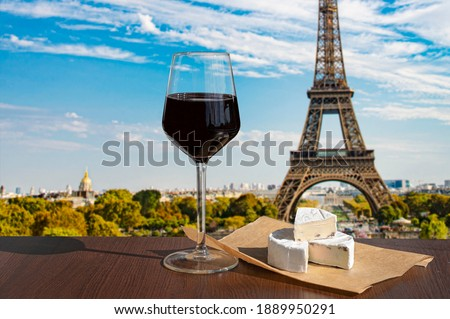 Glass of wine with brie cheese on Eiffel tower and Paris skyline background. Sunny view of glass of red wine overlooking the Eiffel Tower in Paris, France