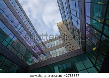 glass office building with sky and clouds reflection