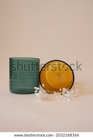 Glass orange and green cups on pink background with decoration. Emerald green cup. Amber orange cup. Couple glass cups with flowers. Tea cups. Coffee cups. Smoothies cup. Water cup.