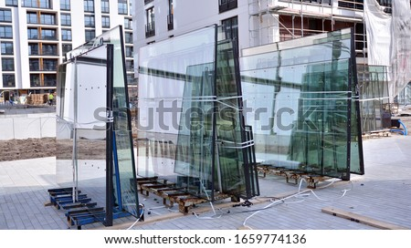 Glass panels in the rack are prepared to be lifted and installed in the building under construction. Double glazed glass window stacked and ready for build in. stock photo