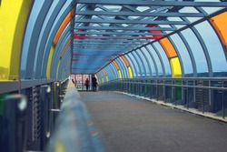Glass pedestrian crossing, overhead passage through the highway. Bright multi-colored glass on a metal frame. New Moscow