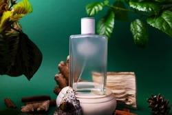 glass perfume bottle on a wooden podium with fragments of wood bark and leaves on a green background. Concept of woody exotic scent