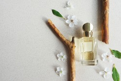 glass perfume bottle on light background with wooden fragments and flowers with sunlight. Summer floral woody perfume concept. Copy space