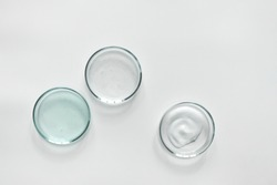 Glass petri dish with different cosmetic products on white background. Shampoo, hair conditioner or mask and shower gel, top view