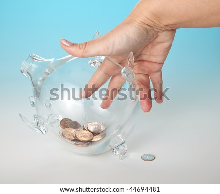 Glass piggy bank with dollars against a blue background and a hand reaching for the money