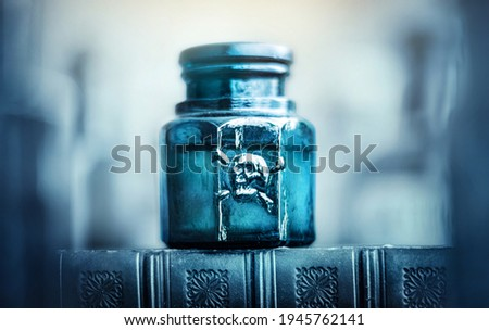 Glass poison bottle with skull and bones. Danger sign, symbol of death. Concept background on poison poisoning, pharmaceutical, chemistry, medical, old science topic. Сток-фото ©