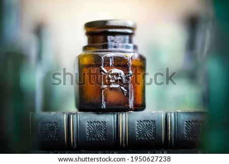 Glass poison bottle with skull and bones. Danger sign, symbol of death. Concept background on poison poisoning, pharmaceutical, chemistry, medical, old science topic.