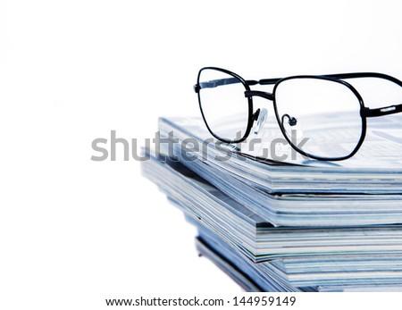 glass put on magazine stack - stock photo