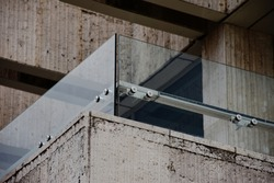 glass railing panel and balustrade above stone panel. balcony railing. laminated tempered safety glass. construction and building industry concept. stainless steel glass brackets.