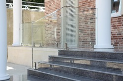 Glass railings on stainless steel support on granite steps. Entrance lobby of a beautiful private house in classic style.