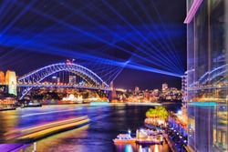 Glass reflection of blue laser lights in dark sky over Sydney harbour and illuminated Sydney harbour bridge from Circular Quay during Vivid Sydney show.