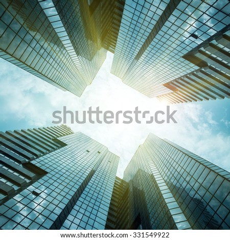 glass reflective office buildings against blue sky with clouds