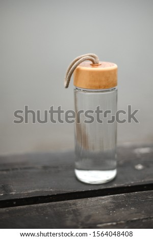 glass reusable bottle for water, stands on a wooden pier against #1564048408