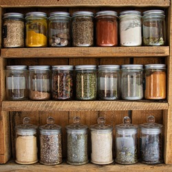 Glass reusable spice jars in a rustic wooden cabinet
