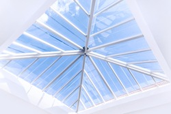 Glass roof modern interior design, abstract background, window in ceiling, luxurious tall building with view on blue sky, contemporary architecture
