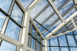 Glass roof of modern office building with outside blue sky