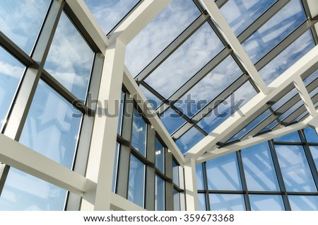 Glass roof of modern office building with outside blue sky #359673368
