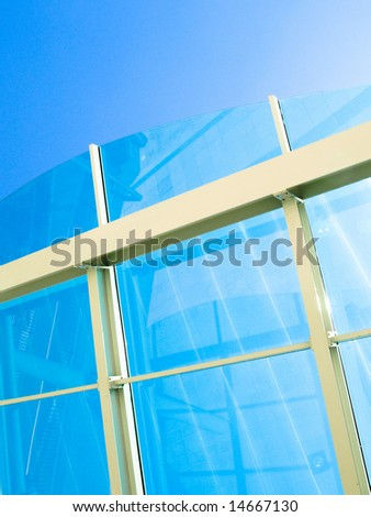Glass roof on blue sky with white metal bars