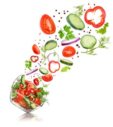 glass salad bowl in flight with vegetables: tomato, pepper, cucumber, onion, dill and parsley. Isolated on white background
