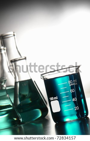 Glass scientific beaker filled with blue chemical liquid and laboratory conical Erlenmeyer flasks for a chemistry experiment in a science research lab
