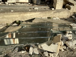 Glass shards and rubble on ground in front of smashed small business storefront