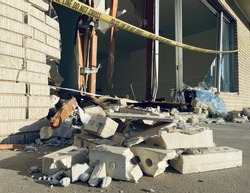 """Glass shards, rubble, and bricks on ground in front of smashed small business storefront draped with """"police line do not cross"""" tape"""