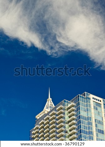 Glass sky scraper with wispy clouds and a deep blue sky