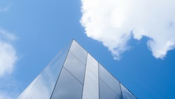 glass structure with blue sky and clouds on the background