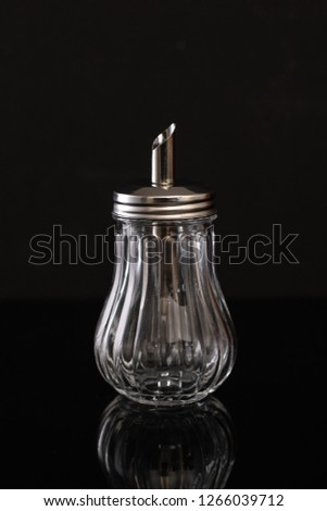 Glass sugar bowl on black background whith reflection #1266039712