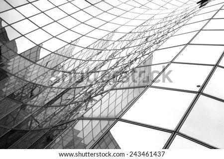 Glass surface of skyscrapers view in district of business centers with reflection on it, black and white  #243461437