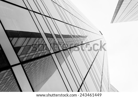 Glass surface of skyscrapers view in district of business centers with reflection on it, black and white  #243461449