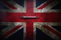 Glass syringe on the background of the British flag. A new stamp of the virus.Photo in retro style.