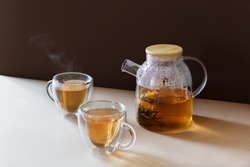 Glass tea pot with flower blooming tea and two tea cups on brown modern background. Hot black tea drink.