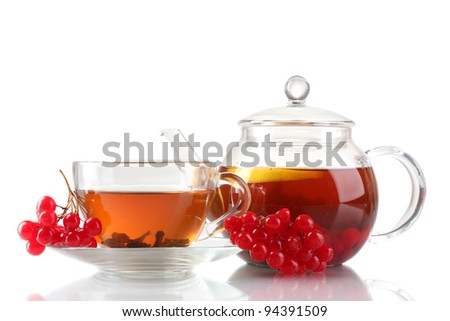 Glass teapot and cup with black viburnum tea isolated on white