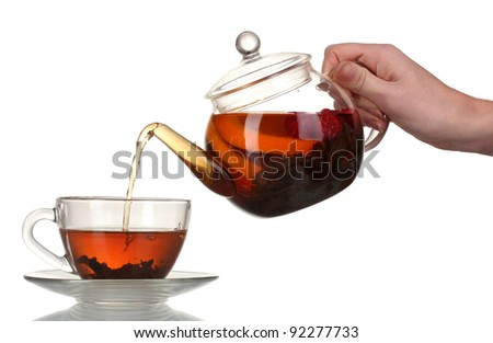 Glass teapot pouring black tea into cup isolated on white