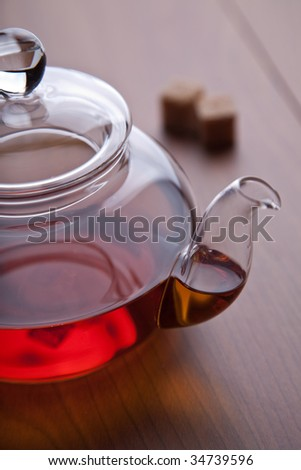 glass teapot with black tea and sugar cubes