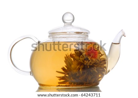 Glass teapot with blooming flower green tea on white background