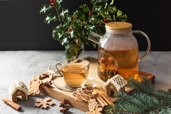Glass teapot with blossoming tea and tea cup on grey table with Christmas gingerbread cookies. Christmas holiday tea ceremony.