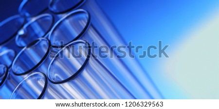 glass test tube on blue background with substance.