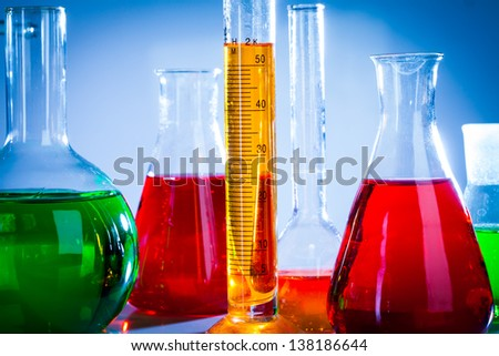 Glass test tubes in the laboratory on a blue background - stock photo