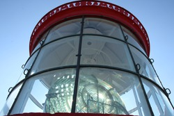glass top and red roof of lighthouse with lighting device at Pointe Saint Mathieu, Brittany blue sky and sunlight