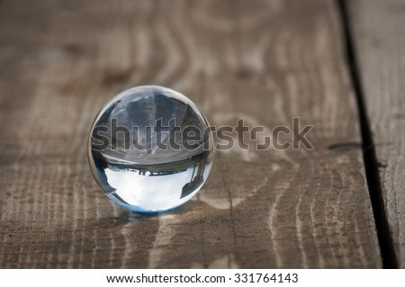 Glass transparent ball on dark background, wooden surface. Soft focus. With empty space for text. #331764143