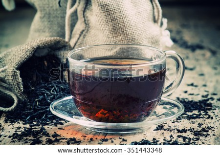 Glass transparent cup of black tea and dry tea in bags on the background of scattered tea leaves on the old wooden background, selective focus