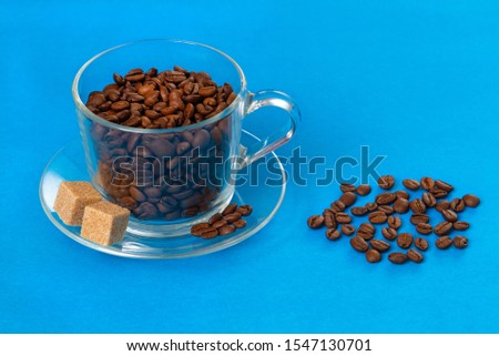 Glass transparent cup with coffee beans with slices of raw sugar sprinkled with coffee grains on a blue background. Copy space. #1547130701
