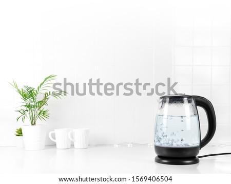 Glass transparent kettle on white kitchen table. Closeup. Nobody Stock photo ©