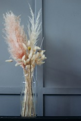 glass transparent vase with dry spikelets. A bouquet of dried flowers.