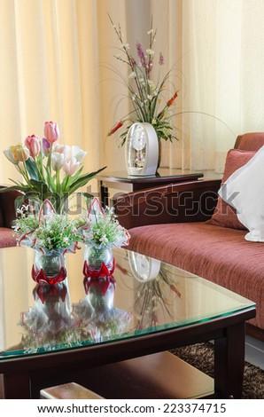 glass vase of flower on glass table in living room