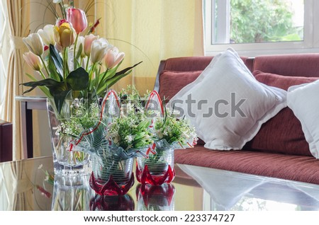 glass vase of flower on glass table with red wooden sofa in living room